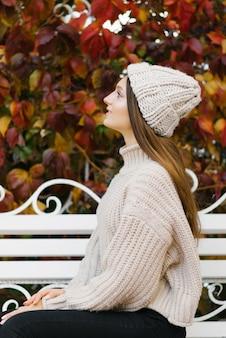 Una giovane donna in un maglione lavorato a maglia si siede su una panchina nel parco