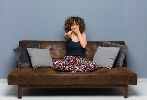 Giovane donna che ride di te, indica e ti prende in giro o ti prende in giro seduto su un divano.