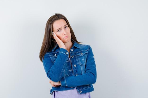 Giovane donna che si appoggia guancia a portata di mano in t-shirt, giacca e sembra delusa, vista frontale.