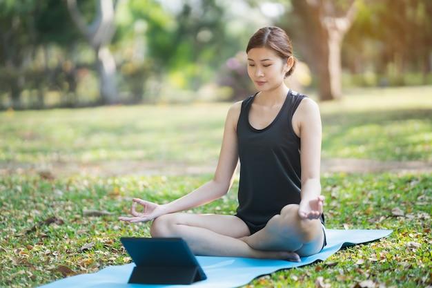 Giovane donna che impara esercizio di yoga in una videoconferenza all'aperto nel parco, concetto di yoga di sport