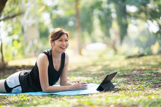 Giovane donna che impara l'esercizio di yoga in una videoconferenza all'aperto nel parco