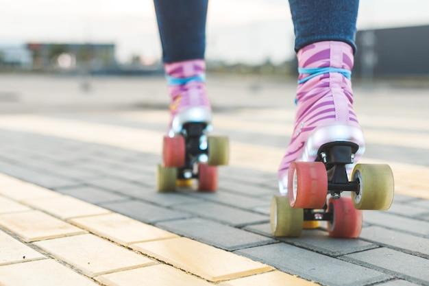 Gambe di giovane donna che cavalcano su pattini a rotelle colorati vista dal basso sul retro