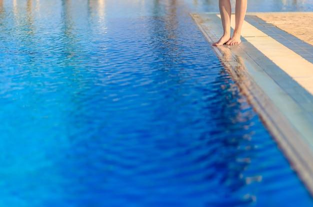 Gambe di giovane donna in piedi sul bordo davanti alla piscina