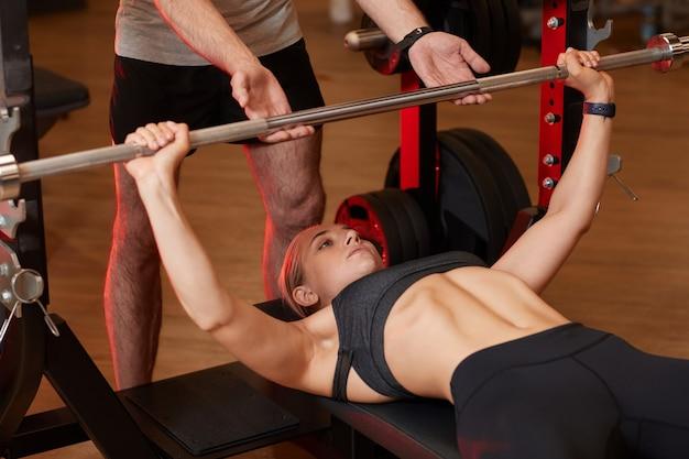 Giovane donna sollevamento manubri con istruttore aiutandola durante l'allenamento sportivo nel centro benessere