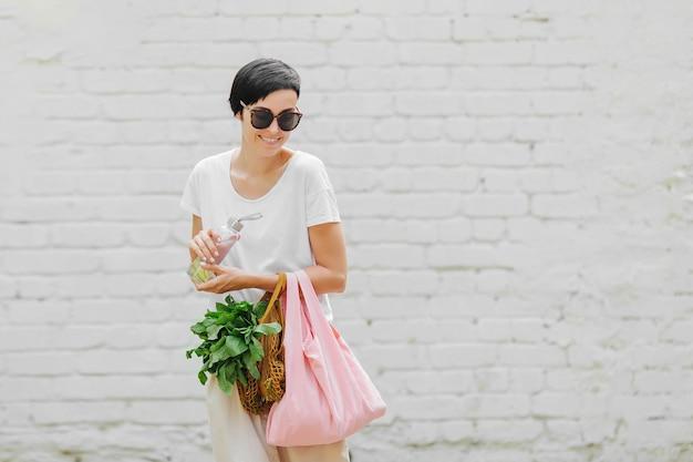 Giovane donna in abiti estivi leggeri con un sacchetto ecologico di verdure, verdure e una bottiglia d'acqua riutilizzabile. stile di vita sostenibile. concetto ecologico.
