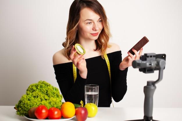 Una giovane donna in lightroom scrive un blog sulla perdita di peso e un'alimentazione sana