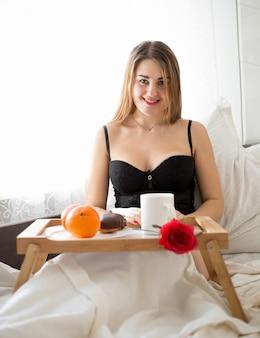 Giovane donna in biancheria che fa colazione in camera d'albergo hotel
