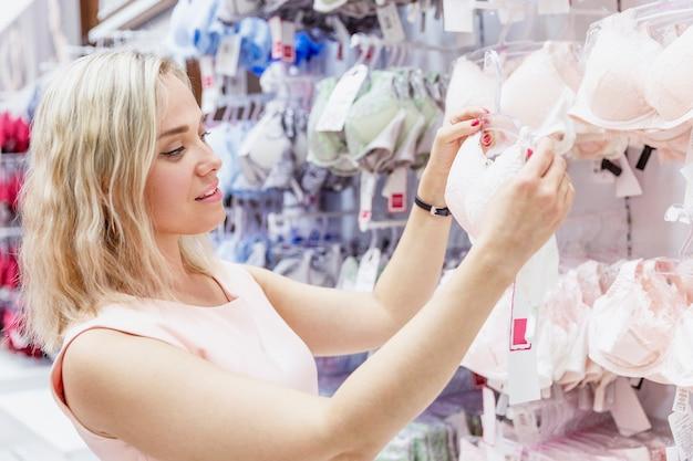 Giovane donna in un negozio di biancheria intima. una bionda sceglie un reggiseno da un vasto assortimento in un centro commerciale.