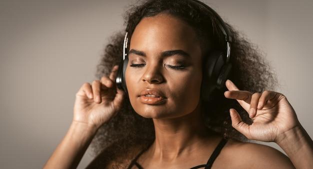 Giovane donna che ascolta la sua traccia preferita in cuffia indossando top nero isolato sul muro grigio crema