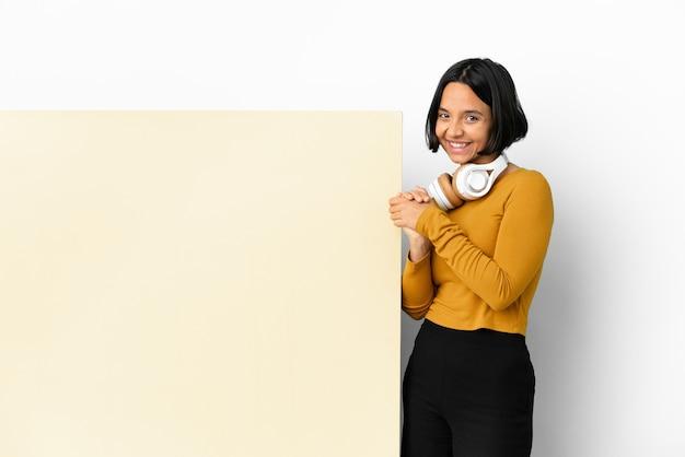 Giovane donna che ascolta musica con un grande cartello vuoto su sfondo isolato applaudire