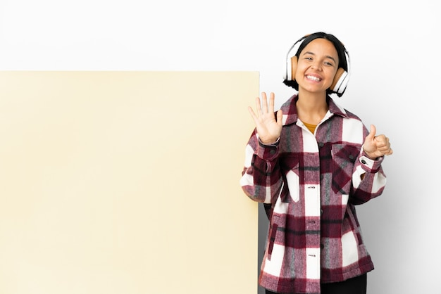 Giovane donna che ascolta musica con un grande cartello vuoto su sfondo isolato contando sei con le dita