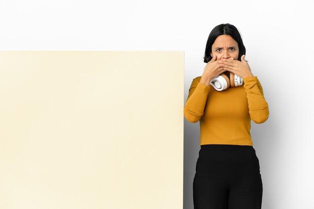 Giovane donna che ascolta musica con un grande cartello vuoto su sfondo isolato che copre la bocca con le mani
