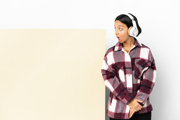 Giovane donna che ascolta musica con un grande cartello vuoto su sfondo isolato che fa un gesto a sorpresa mentre guarda di lato