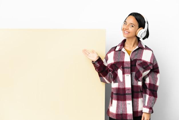 Giovane donna che ascolta musica con un grande cartello vuoto su sfondo isolato che estende le mani di lato per invitare a venire
