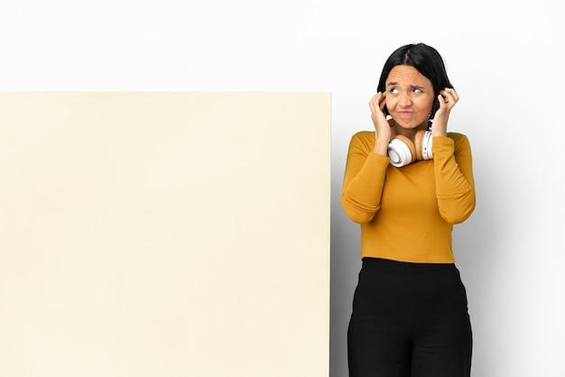 Giovane donna che ascolta musica con un grande cartello vuoto su sfondo isolato frustrato e che copre le orecchie