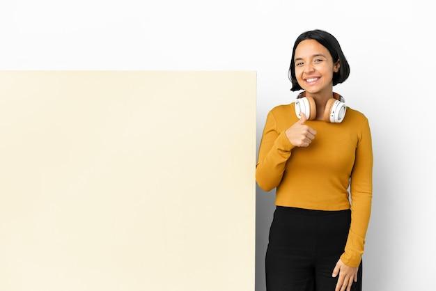 Giovane donna che ascolta musica con un grande cartello vuoto su sfondo isolato che dà un gesto di pollice in alto