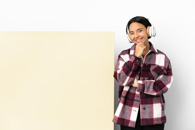 Giovane donna che ascolta musica con un grande cartello vuoto su sfondo isolato felice e sorridente