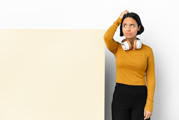 Giovane donna che ascolta musica con un grande cartello vuoto su sfondo isolato che ha dubbi mentre si gratta la testa