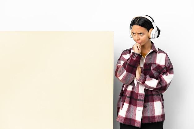 Giovane donna che ascolta musica con un grande cartello vuoto su sfondo isolato avendo dubbi