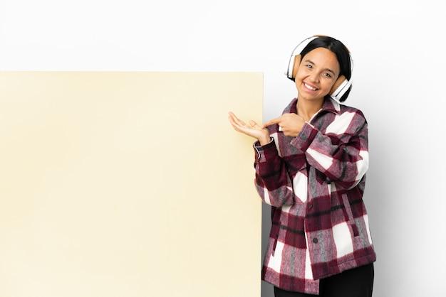 Giovane donna che ascolta musica con un grande cartello vuoto su sfondo isolato che tiene copyspace immaginario sul palmo per inserire un annuncio