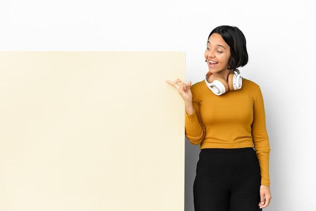 Giovane donna che ascolta musica con un grande cartello vuoto su sfondo isolato con l'intenzione di realizzare la soluzione mentre si solleva un dito
