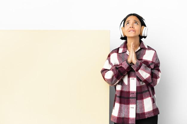 La musica d'ascolto della giovane donna con un grande cartello vuoto sopra fondo isolato tiene insieme il palmo. la persona chiede qualcosa
