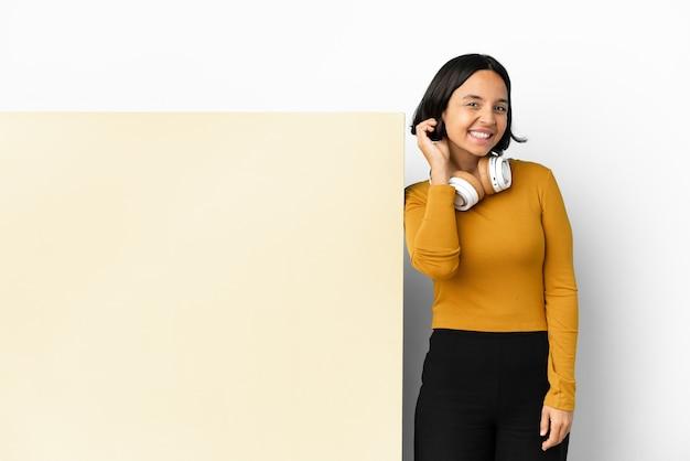 Giovane donna che ascolta musica con un grande cartello vuoto su sfondo isolato ridendo
