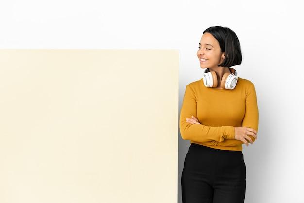 Giovane donna che ascolta musica con un grande cartello vuoto su sfondo isolato guardando di lato e sorridente