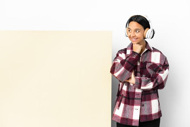 Giovane donna che ascolta musica con un grande cartello vuoto su sfondo isolato guardando in alto mentre sorride