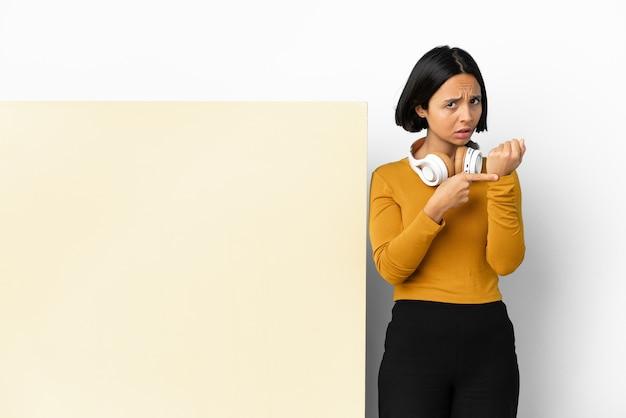 Giovane donna che ascolta musica con un grande cartello vuoto su sfondo isolato facendo il gesto di essere in ritardo