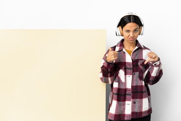 Musica d'ascolto della giovane donna con un grande cartello vuoto sopra fondo isolato che fa il segno buono-cattivo. indeciso tra si o no
