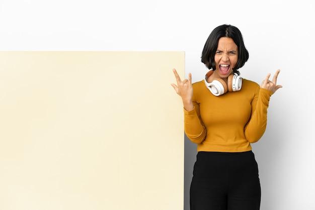 Musica d'ascolto della giovane donna con un grande cartello vuoto sopra fondo isolato che fa il gesto del corno