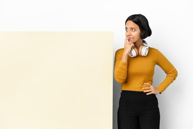 Giovane donna che ascolta musica con un grande cartello vuoto su sfondo isolato nervoso e spaventato