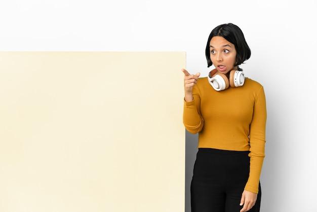 Giovane donna che ascolta musica con un grande cartello vuoto su sfondo isolato che punta lontano