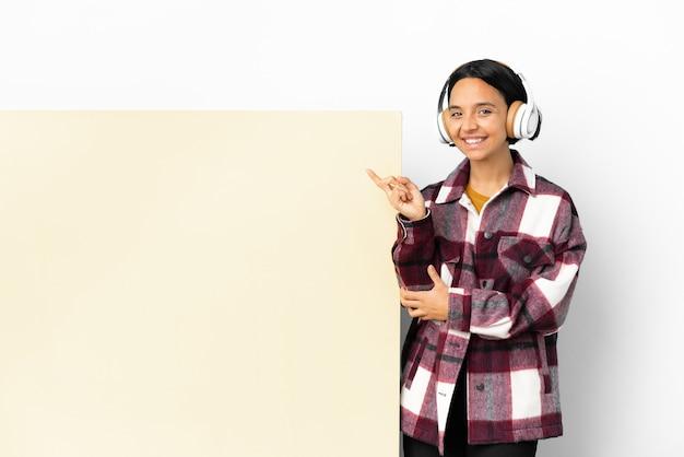 Giovane donna che ascolta musica con un grande cartello vuoto su sfondo isolato che punta il dito sul lato