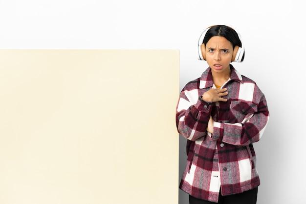 Giovane donna che ascolta musica con un grande cartello vuoto su sfondo isolato che punta a se stesso