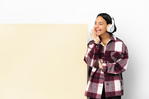 Giovane donna che ascolta musica con un grande cartello vuoto su uno sfondo isolato che grida con la bocca spalancata di lato