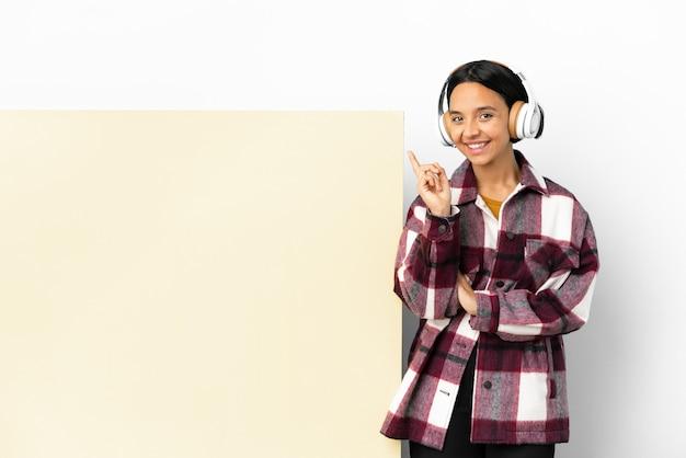 Giovane donna che ascolta musica con un grande cartello vuoto su sfondo isolato che mostra e solleva un dito in segno del meglio