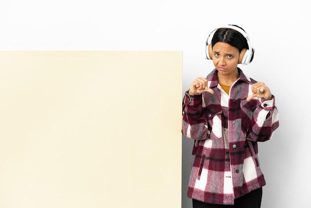 Giovane donna che ascolta musica con un grande cartello vuoto su sfondo isolato che mostra il pollice verso il basso con due mani