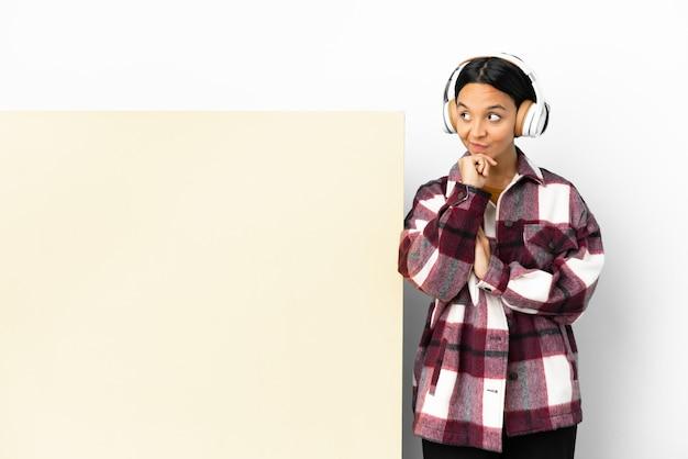 Giovane donna che ascolta musica con un grande cartello vuoto su sfondo isolato pensando a un'idea mentre guarda in alto