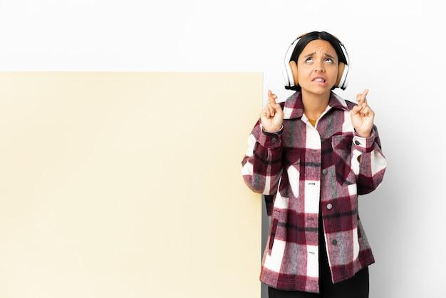 Giovane donna che ascolta musica con un grande cartello vuoto su sfondo isolato con le dita incrociate e augurando il meglio