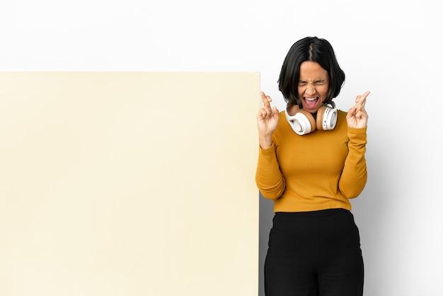 Giovane donna che ascolta musica con un grande cartello vuoto su sfondo isolato con le dita che si incrociano