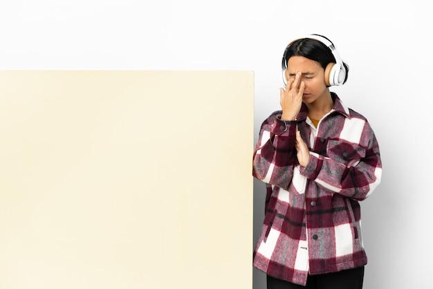 Giovane donna che ascolta musica con un grande cartello vuoto su sfondo isolato con mal di testa
