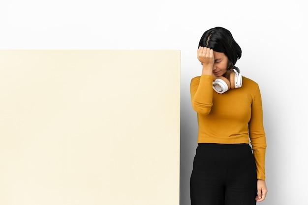 Musica d'ascolto della giovane donna con un fondo isolato grande cartello vuoto con mal di testa