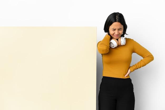 Giovane donna che ascolta musica con un grande cartello vuoto su sfondo isolato con mal di collo