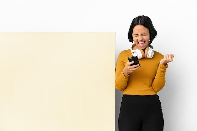 Giovane donna che ascolta musica con un grande cartello vuoto su sfondo isolato con telefono in posizione di vittoria