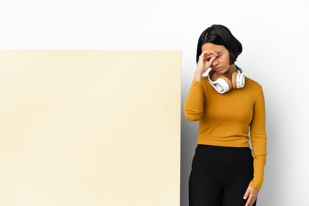 Giovane donna che ascolta musica con un grande cartello vuoto su sfondo isolato con espressione stanca e malata