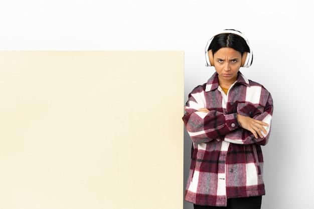 Giovane donna che ascolta musica con un grande cartello vuoto su sfondo isolato con espressione infelice