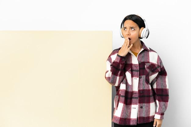 Giovane donna che ascolta musica con un grande cartello vuoto su sfondo isolato che sbadiglia e che copre la bocca spalancata con la mano