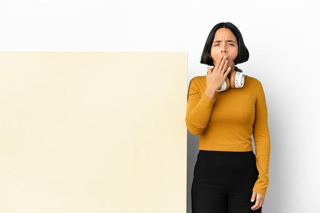 Giovane donna che ascolta musica con un grande cartello vuoto su sfondo isolato che sbadiglia e copre la bocca spalancata con la mano